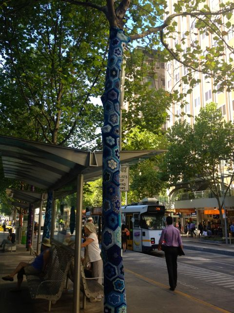 A blue granny blanket at the tram and bus stop.